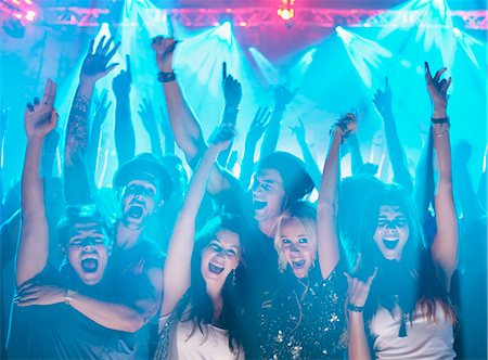 Portrait of enthusiastic crowd with arms raised at concert Stock Photo - Premium Royalty-Free, Code: 6113-06498631
