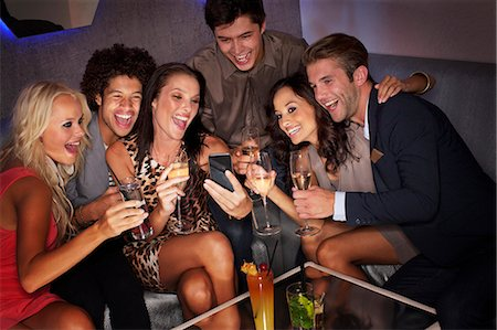 Smiling friends drinking cocktails and looking down at cell phone in nightclub Stock Photo - Premium Royalty-Free, Code: 6113-06498703