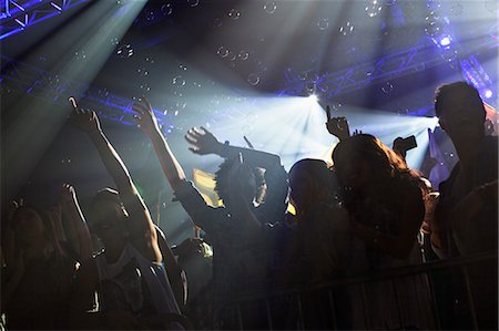 Crowd cheering with arms raised at concert Stock Photo - Premium Royalty-Free, Code: 6113-06498705