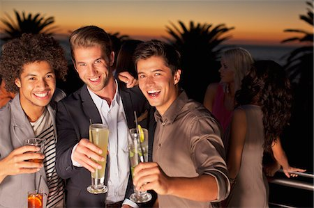 exterior bar - Portrait of smiling men toasting cocktails on balcony at sunset Stock Photo - Premium Royalty-Free, Code: 6113-06498710