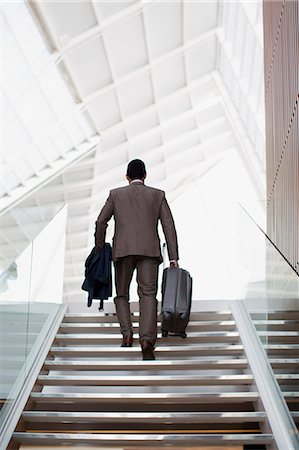 Businessman with suitcase ascending stairs Stock Photo - Premium Royalty-Free, Code: 6113-06498841