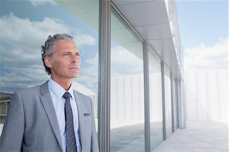 Pensive businessman outside building Stock Photo - Premium Royalty-Free, Code: 6113-06498844