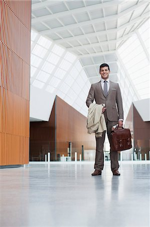 Portrait of smiling businessman holding coat and briefcase in lobby Stock Photo - Premium Royalty-Free, Code: 6113-06498870
