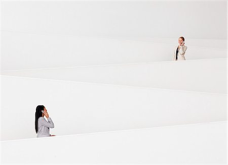filipina - Businesswomen talking on cell phones on modern staircase Stock Photo - Premium Royalty-Free, Code: 6113-06498878