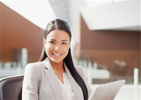 filipina - Portrait of smiling businesswoman using digital tablet in office Stock Photo - Premium Royalty-Free, Code: 6113-06498891