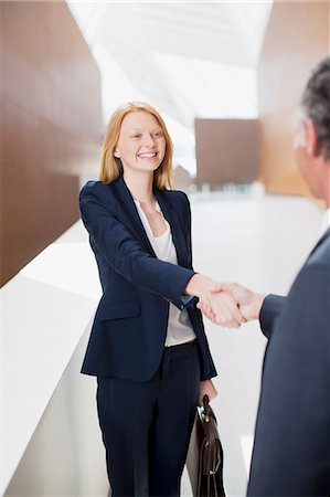 Smiling businesswoman shaking hands with businessman Stock Photo - Premium Royalty-Free, Code: 6113-06498821