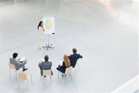 Businesswoman at flipchart leading meeting in lobby Stock Photo - Premium Royalty-Free, Code: 6113-06498822
