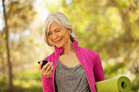 Older woman using cell phone outdoors Stock Photo - Premium Royalty-Free, Code: 6113-06499079