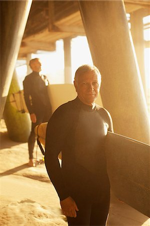 Older surfers carrying boards under pier Stock Photo - Premium Royalty-Free, Code: 6113-06499098