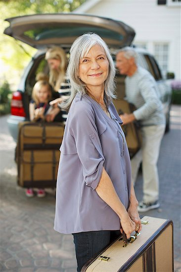 Woman carrying suitcase to trunk Stock Photo - Premium Royalty-Free, Image code: 6113-06499012