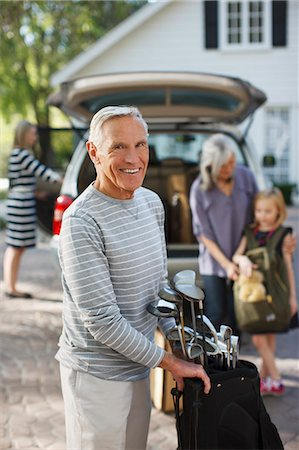 Older man carrying golf clubs in bag Stock Photo - Premium Royalty-Free, Code: 6113-06499018