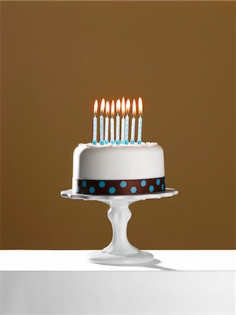 Birthday cake with lit candles on cake stand Stock Photo - Premium Royalty-Free, Code: 6113-06499143