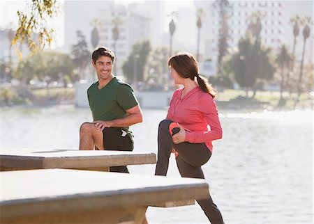 Couple stretching together in park Stock Photo - Premium Royalty-Free, Code: 6113-06499141