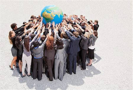 Crowd of business people in huddle reaching for globe Stock Photo - Premium Royalty-Free, Code: 6113-06499150