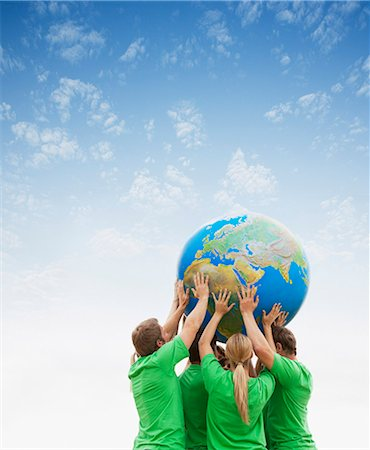 Team in green t-shirts lifting globe overhead Stock Photo - Premium Royalty-Free, Code: 6113-06499152