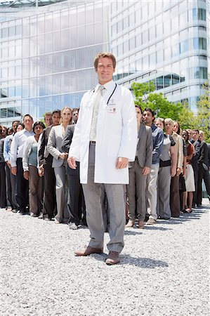 partnership - Portrait of smiling doctor with business people in background Stock Photo - Premium Royalty-Free, Code: 6113-06499158
