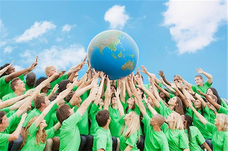 Team in green t-shirts lifting globe overhead Stock Photo - Premium Royalty-Free, Code: 6113-06499166