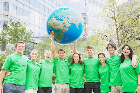 Portrait of team in green t-shirts lifting globe overhead Stock Photo - Premium Royalty-Free, Code: 6113-06499185