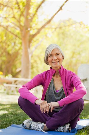 Older woman sitting on yoga mat outdoors Stock Photo - Premium Royalty-Free, Code: 6113-06499117
