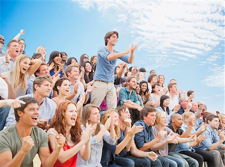 Man standing and clapping among cheering crowd Stock Photo - Premium Royalty-Free, Code: 6113-06499205