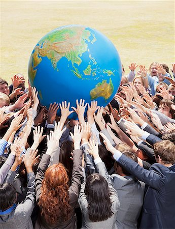 Crowd of business people reaching for globe Stock Photo - Premium Royalty-Free, Code: 6113-06499215