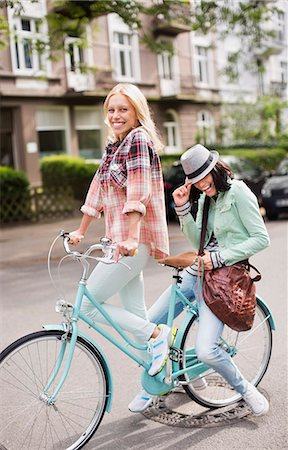 Women riding bicycle together on city street Stock Photo - Premium Royalty-Free, Code: 6113-06625559