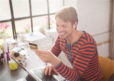 ebusiness - Man in headphones shopping on laptop Stock Photo - Premium Royalty-Free, Code: 6113-06625563