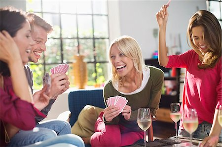 Friends playing card game in living room Stock Photo - Premium Royalty-Free, Code: 6113-06625560