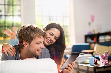 Couple using digital tablet on sofa Stock Photo - Premium Royalty-Free, Code: 6113-06625571