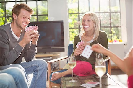 Friends playing card game in living room Stock Photo - Premium Royalty-Free, Code: 6113-06625581