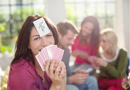 Smiling woman playing card game Stock Photo - Premium Royalty-Free, Code: 6113-06625611