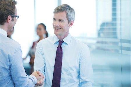 Businessmen shaking hands in office Stock Photo - Premium Royalty-Free, Code: 6113-06625784