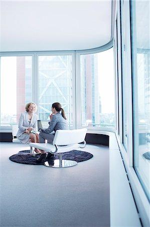 Businesswomen talking in office lobby Stock Photo - Premium Royalty-Free, Code: 6113-06625819
