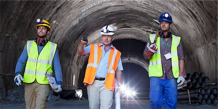 Businessman and workers walking in tunnel Stock Photo - Premium Royalty-Free, Code: 6113-06625946
