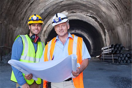 Workers reading blueprints in tunnel Stock Photo - Premium Royalty-Free, Code: 6113-06625912