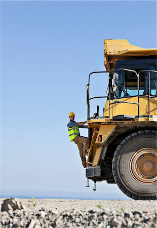 Worker climbing machinery in quarry Stock Photo - Premium Royalty-Free, Code: 6113-06625916