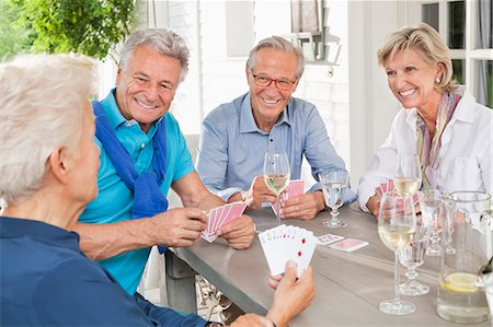 Friends playing card games at table Stock Photo - Premium Royalty-Free, Code: 6113-06626382