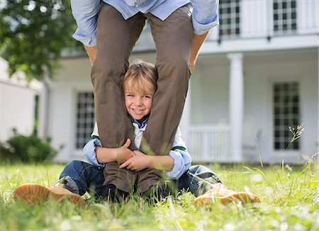 Boy peeking out from between father's legs Stock Photo - Premium Royalty-Free, Code: 6113-06626304