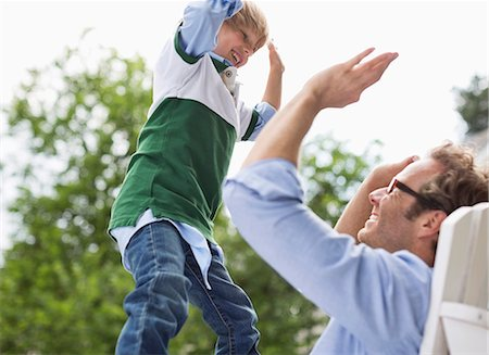 Father and son high fiving outdoors Stock Photo - Premium Royalty-Free, Code: 6113-06626339