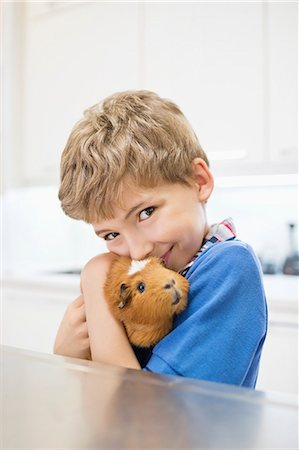 Boy cuddling guinea pig in vet's surgery Stock Photo - Premium Royalty-Free, Code: 6113-06626486