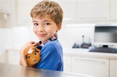 Boy holding guinea pig in vet's surgery Stock Photo - Premium Royalty-Free, Code: 6113-06626491
