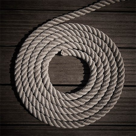 Rope coiled into circle on boardwalk Stock Photo - Premium Royalty-Free, Code: 6113-06626626