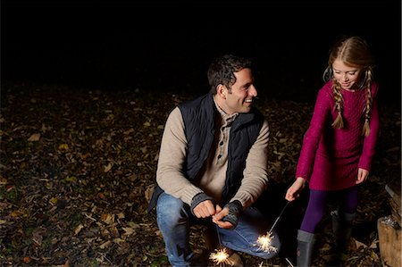 spark - Father and daughter playing with sparklers Stock Photo - Premium Royalty-Free, Code: 6113-06626737