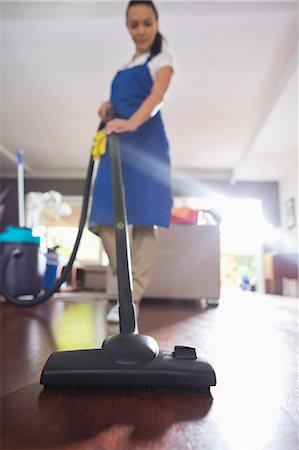 Woman vacuuming living room floor Stock Photo - Premium Royalty-Free, Code: 6113-06753243