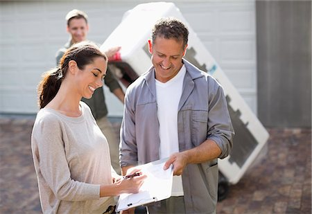Woman signing for delivery in driveway Stock Photo - Premium Royalty-Free, Code: 6113-06753244