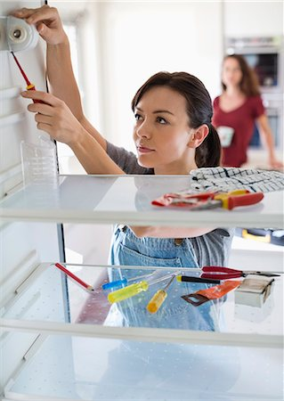 diy or home improvement - Female repair person working on fridge in home Stock Photo - Premium Royalty-Free, Code: 6113-06753252