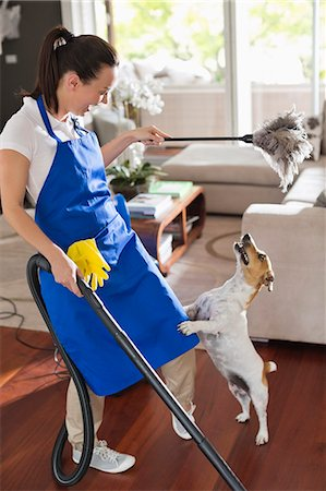 Maid playing with dog in living room Stock Photo - Premium Royalty-Free, Code: 6113-06753255