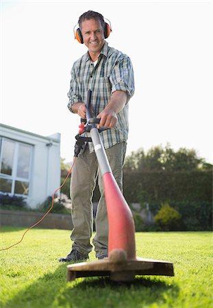 Man using weed whacker in backyard Stock Photo - Premium Royalty-Free, Code: 6113-06753258