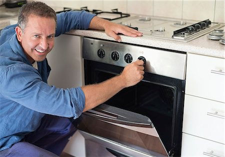 stove - Electrician working on oven in kitchen Stock Photo - Premium Royalty-Free, Code: 6113-06753274