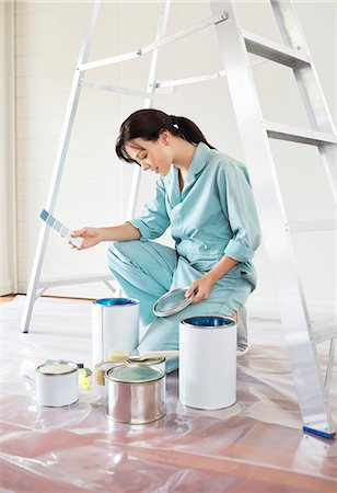 painter - Woman examining paint cans Stock Photo - Premium Royalty-Free, Code: 6113-06753210